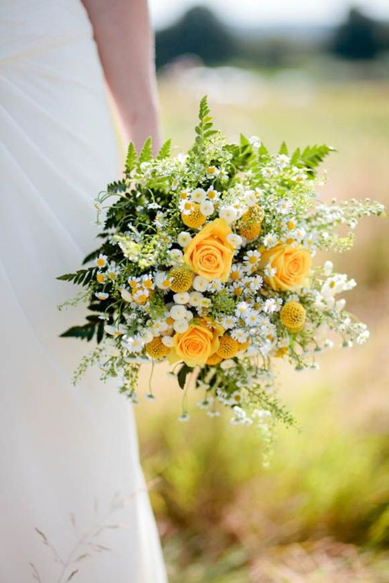 a bright and chic wedding bouquet that includes yellow roses, billy balls, daisies, ferns and greenery for a summer wedding