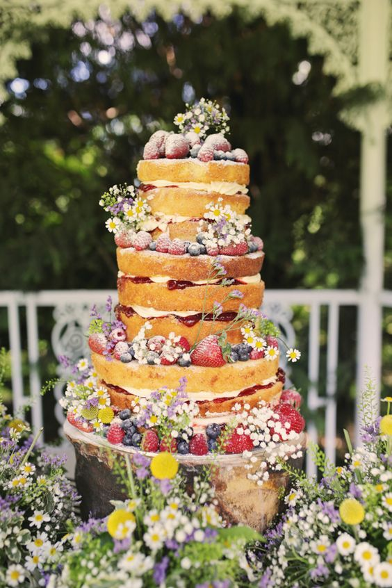 a naked secret garden wedding cake decorated with bold blooms and fresh berries is a very chic and delicious-looking idea