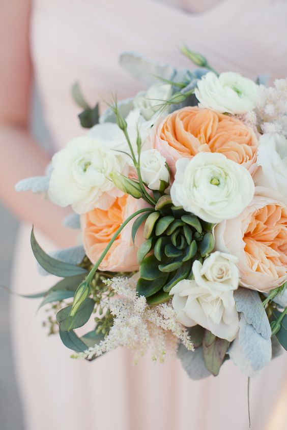 a romantic wedding bouquet of peachy peonies and white ranunculus, succulents and greenery is a cool and fresh idea to rock