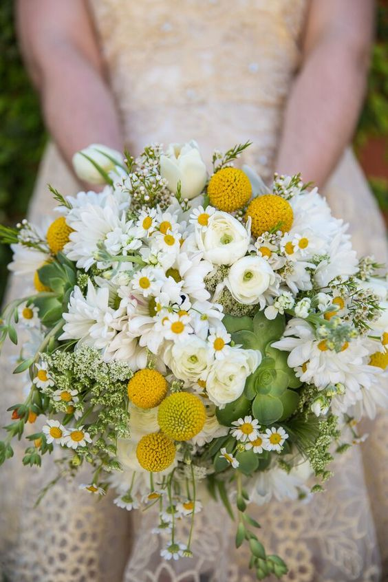 a bright and dimensional summer wedding bouquet of daisies, billy balls, white blooms, succulents, greenery and ranunculus is a fun and fresh idea