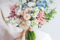 13 a dreamy wedding bouquet of white peonies, blush and white ranunculus, astilbe, blue blooms and blush ribbons for a garden bride