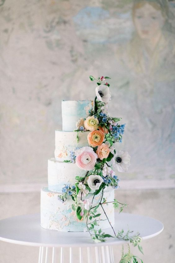 a refined secret garden wedding cake with textural blue buttercream and pastel detailing, pastel blooms and greenery