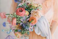 14 a bright and chic wedding bouquet of pink and orange ranunculus, blue and purple blooms, greenery and blue ribbons