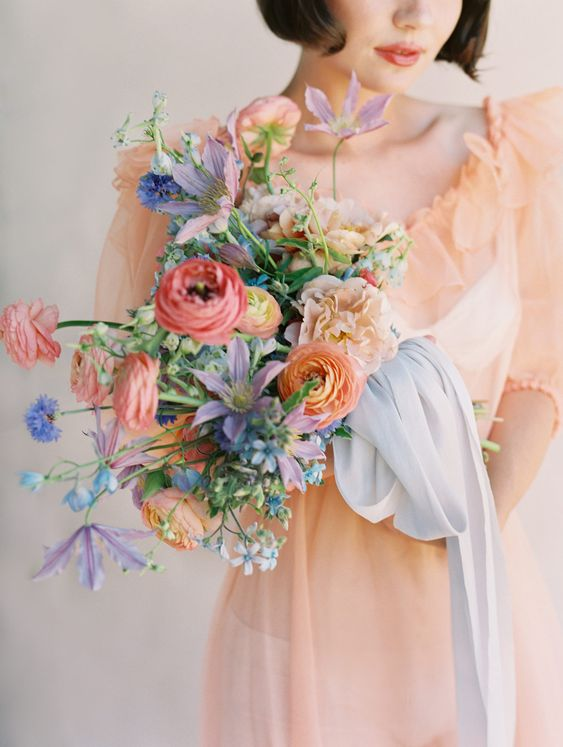 a bright and chic wedding bouquet of pink and orange ranunculus, blue and purple blooms, greenery and blue ribbons