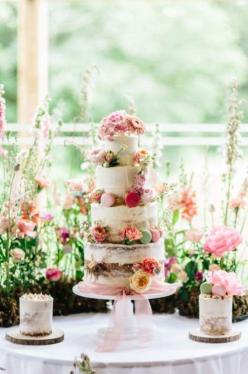 a romantic secret garden wedding cake - a naked one with bold blooms and colorful macarons plus pink ribbons is wow