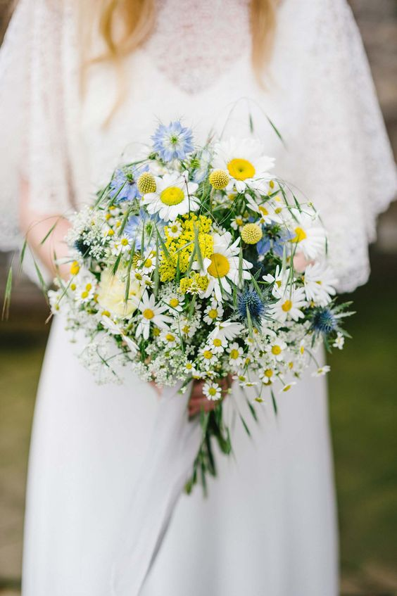 a midsummer wedding bouquet with daisies, blue blooms and yellow mimosas, grass is a very lovely and relaxed arrangement