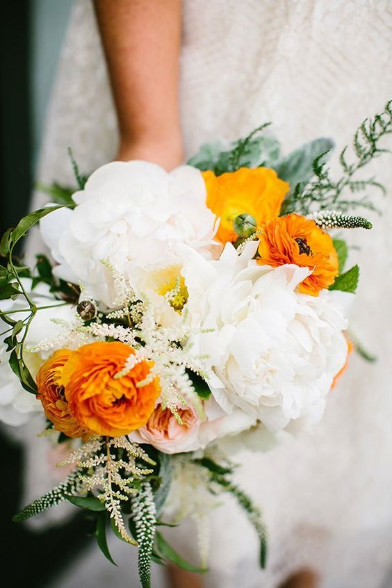 a bold wedding bouquet with white peonies, orange ranunculus, greenery, astilbe is a fresh and cool bouquet for summer