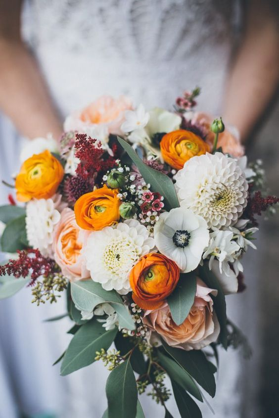 a bright and cool wedding bouquet with white anemones and dahlias, orange ranunculus, waxflowers and greenery for a bright wedding