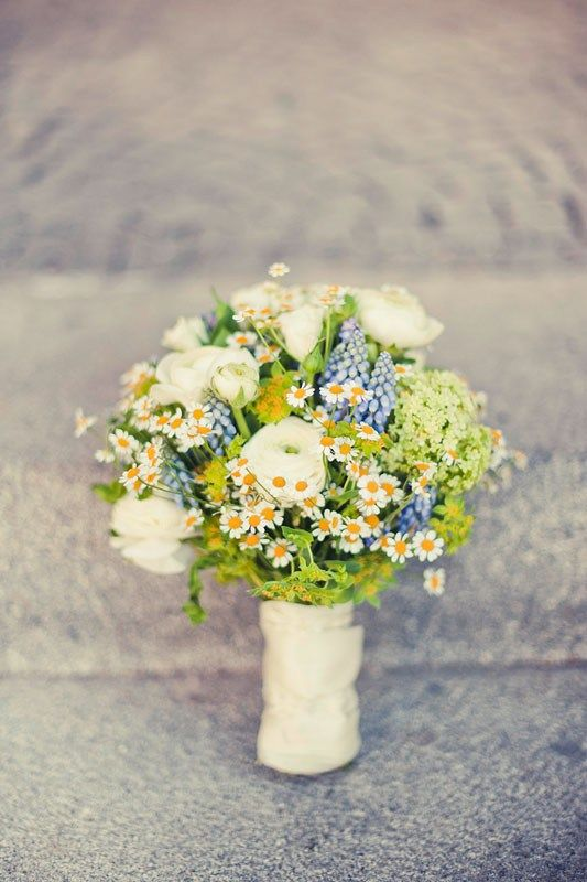 a pretty summer wedding bouquet with daisies, blue blooms and white ranunculus, some greenery is a lovely rustic summer idea