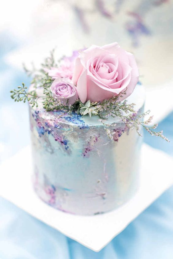 a very delicate and refined pastel wedding cake in light blue, with pink roses and greenery and sugar detailing is amazing for a secret garden wedding