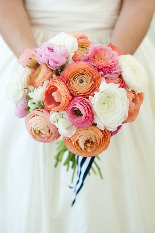 a bright ranunculus wedding bouquet that includes white, orange, pink blooms and striped ribbons is lovely for summer