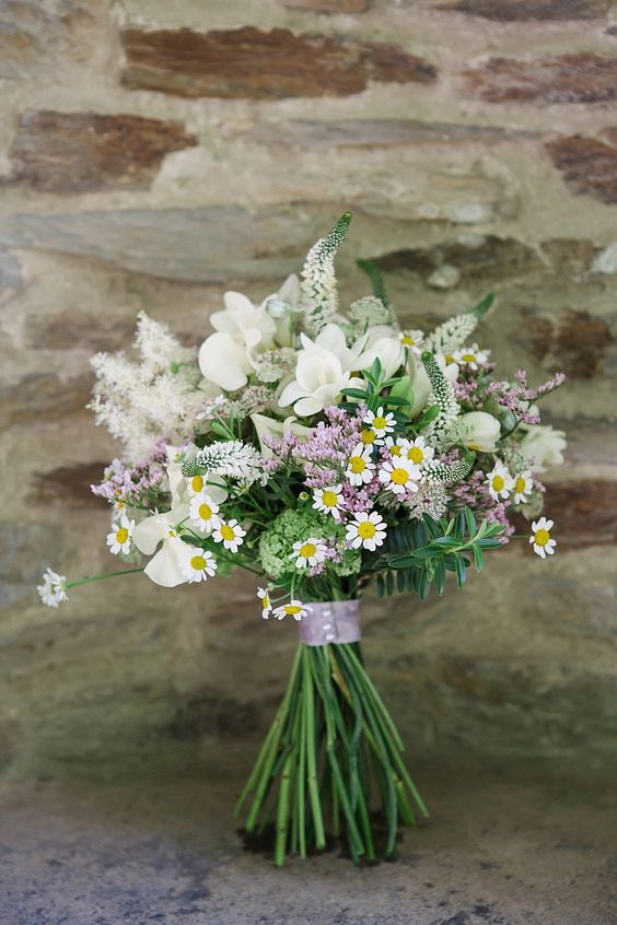 a relaxed summer wedding bouquet of white and pink blooms, astilbe and daisies plus a lilac wrap is a fresh and lovely option
