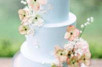 18 a very delicate pastel blue wedding cake with fresh white and peachy blooms and baby's breath is amazing for a secret garden wedding