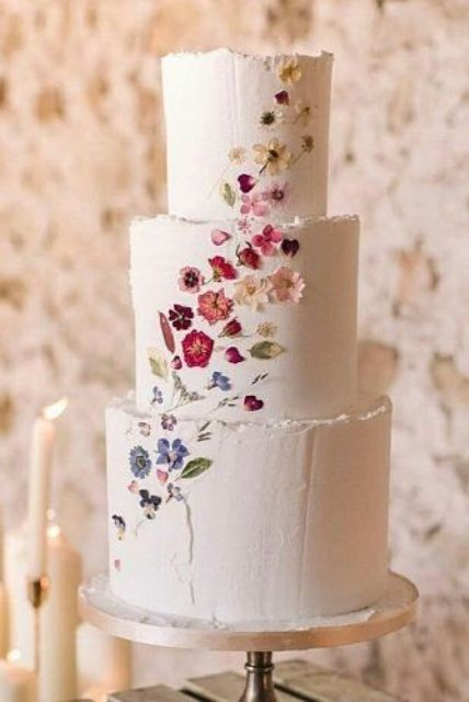 a white buttercream wedding cake with a raw edge and bright pressed blooms looks refined and very chic