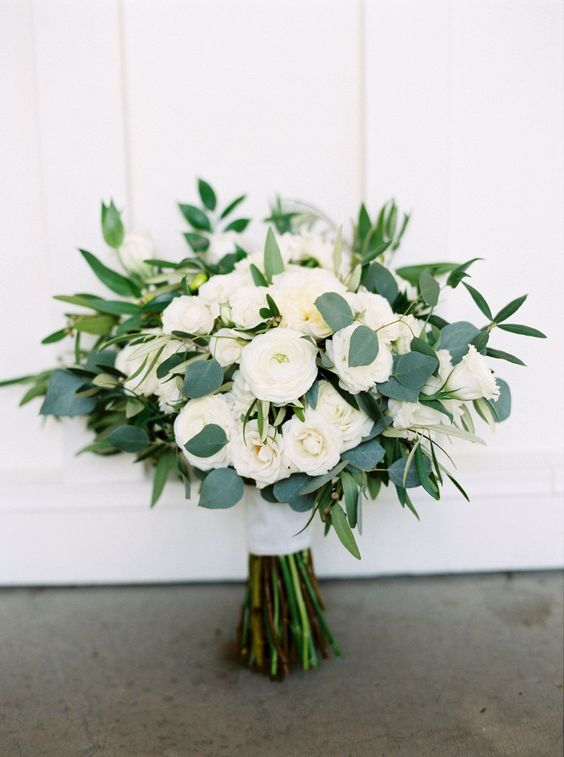 a beautiful and dreamy white ranunculus wedding bouquet spruced up with some eucalyptus is a chic and lovely idea
