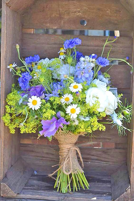 a bright wedding bouquet of daisies, sweet peas, ranunculus, mimosas and greenery looks wild and very creative