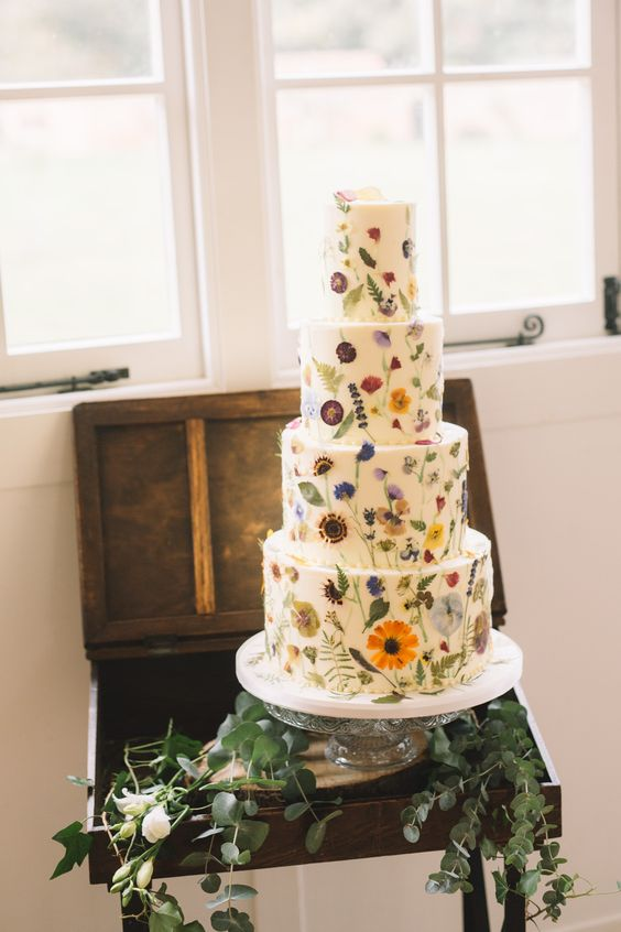 a gorgeous white wedding cake with lots of bright pressed blooms and leaves is a fantastic solution for a relaxed garden wedding