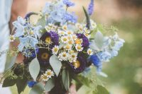 21 a bright wedding bouquet with daisies, purple and blue flowers and eucalyptus is a bold and super cool idea