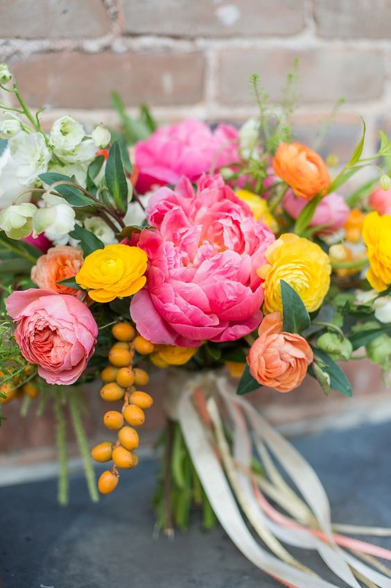 a colorful wedding bouquet with bright pink peonies, yellow and orange ranunculus, berries and white blooms and lots of greenery