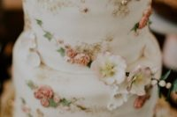 21 a delicate and refined white wedding cake decorated with natural and sugar blooms, with sugar leaves and birdie toppers