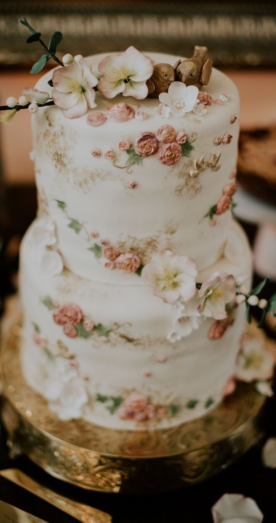 a delicate and refined white wedding cake decorated with natural and sugar blooms, with sugar leaves and birdie toppers