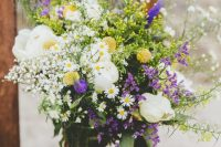 22 a bright wedding bouquet with purple and yellow blooms, daisies, white peonies, greenery and billy balls is a cool idea for a boho wedding