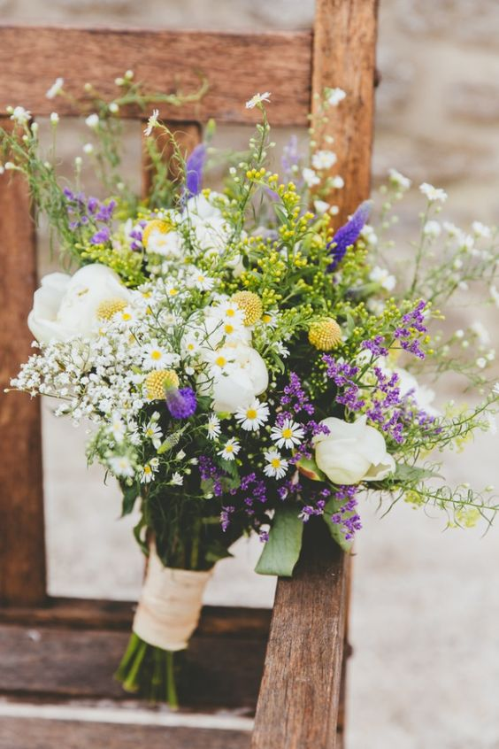 a bright wedding bouquet with purple and yellow blooms, daisies, white peonies, greenery and billy balls is a cool idea for a boho wedding