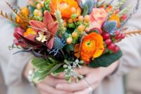 22 a colorful wedding bouquet with orange ranunculus, thistles, dark lilies, berries and grasses for a color-loving bride