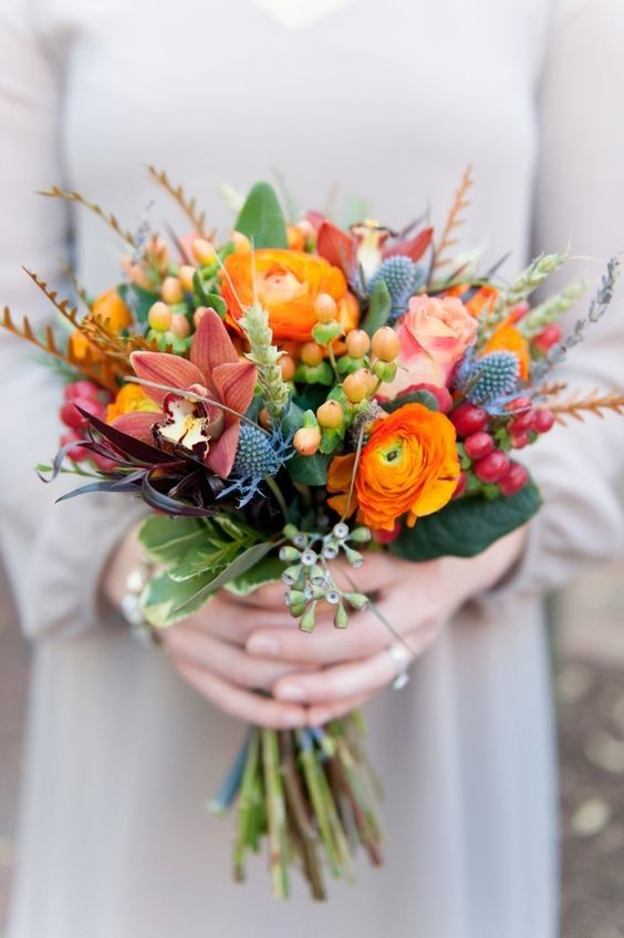 a colorful wedding bouquet with orange ranunculus, thistles, dark lilies, berries and grasses for a color-loving bride