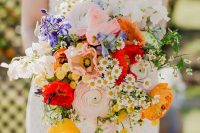23 a colorful wedding bouquet with pink and yellow ranunculus, white and blush blooms, bold red touches and greenery