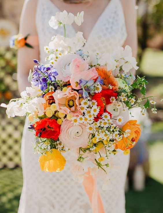 a colorful wedding bouquet with pink and yellow ranunculus, white and blush blooms, bold red touches and greenery