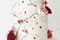 23 a fancy wedding cake with pressed bright blooms and sugar flowers and leaves surrounding it is a refined and chic idea