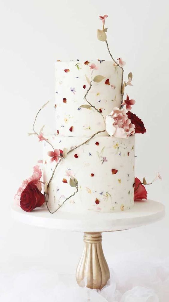 a fancy wedding cake with pressed bright blooms and sugar flowers and leaves surrounding it is a refined and chic idea