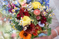 24 a colorful summer wedding bouquet that includes orange, yellow, burgundy, blue and purple blooms and some daisies as fillers