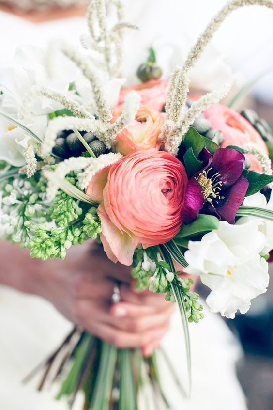 a colorful wedding bouquet with pink ranunculus, purple blooms, berries, lots of greenery and creative fillers is amazing