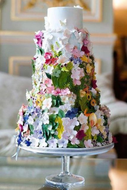 a gorgeous secret garden wedding cake decorated with bold and pastel sugar blooms and leaves is a lovely idea