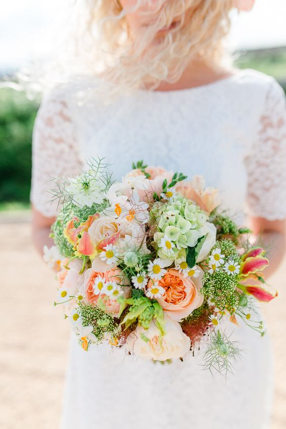 a colorful summer wedding bouquet with peachy and pink peonies, daisies, greenery, green hydrangeas and coral lilies is fun