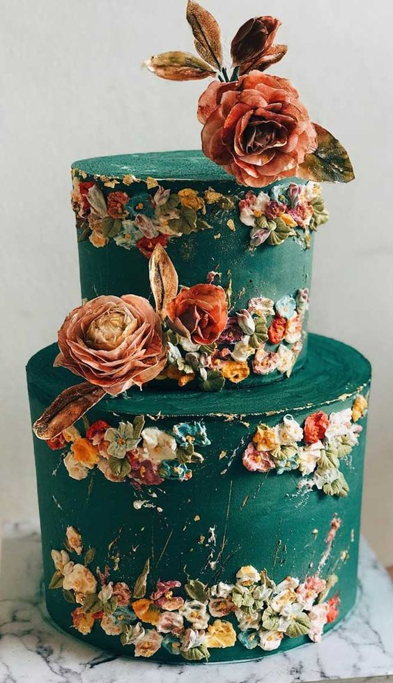 a green buttercream wedding cake with pastel sugar blooms and real ones is a jaw dropping option for a secret garden wedding