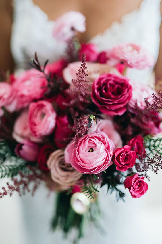 a jewel-tone wedding bouquet of pink ranunculus and fuchsia roses, some dark and usual foliage is amazing for fall