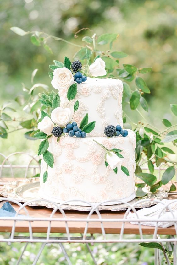 a heavenly secret garden wedding cake with sugar floral detailing, fresh berries and some foliage is a delicate and refined idea
