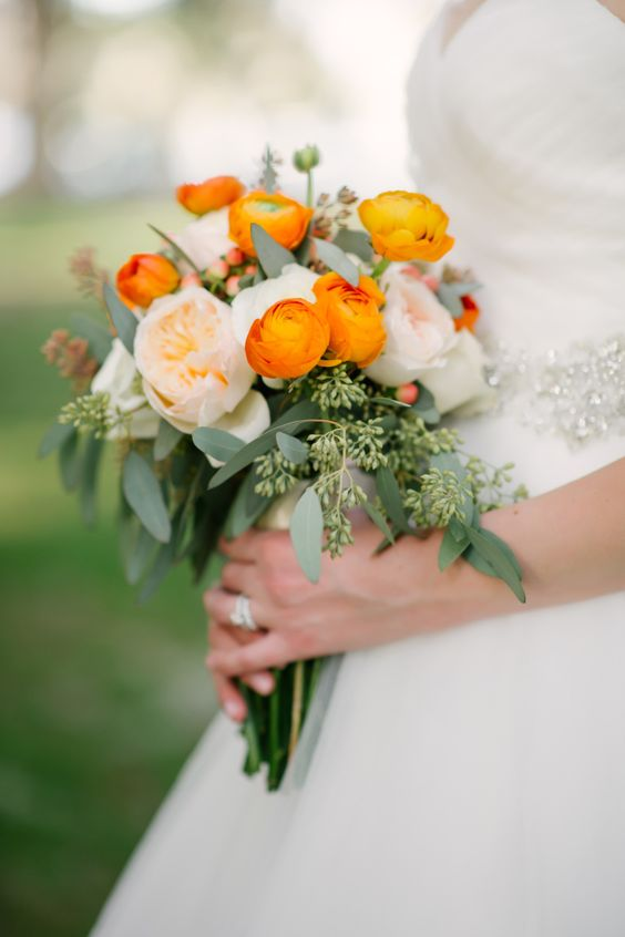 a lovely wedding bouquet of blush peonies, orange ranunculus and greenery is amazing and super bold