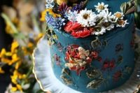 27 a jaw-dropping secret garden wedding cake in blue, with lots of sugar blooms and leaves of various colors is amazing