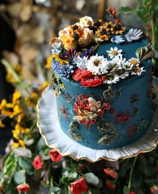 a jaw-dropping secret garden wedding cake in blue, with lots of sugar blooms and leaves of various colors is amazing