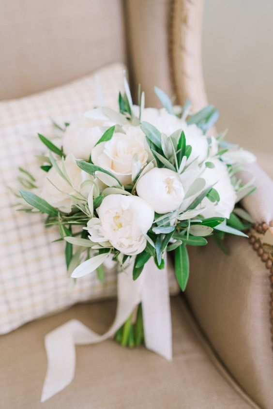 a white peony wedding bouquet with some greenery is a fresher idea than just peonies and it looks cuter and more modern