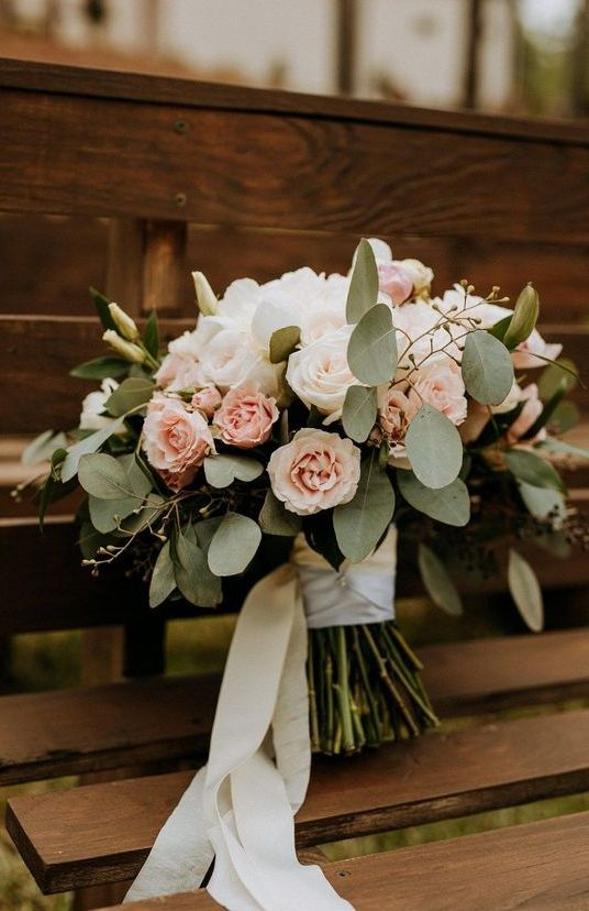 a white rose and blush rose wedding bouquet refreshed with eucalyptus and white ribbons looks very dreamy and very chic