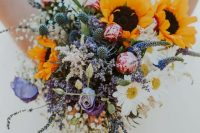 29 a gorgeous summer wedding bouquet of sunflowers, purple and pink blooms, lavender, baby's breath, thistles and daisies is lovely