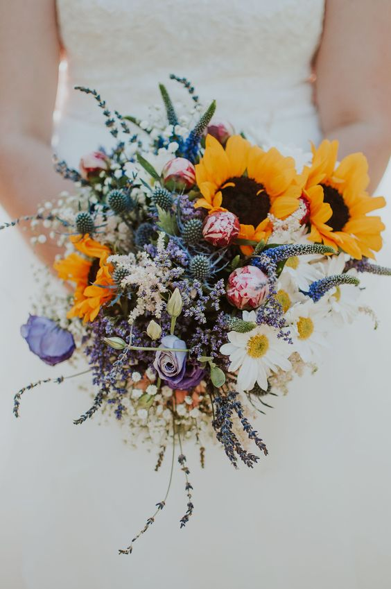 a gorgeous summer wedding bouquet of sunflowers, purple and pink blooms, lavender, baby's breath, thistles and daisies is lovely