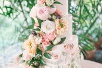 29 a lush and luxurious secret garden wedding cake with sugar blooms and with lush pastel flowers and foliage is wow