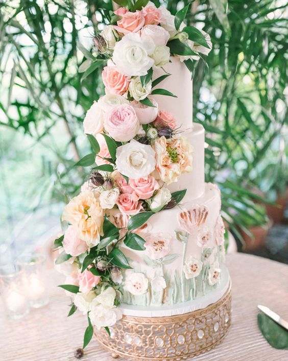 a lush and luxurious secret garden wedding cake with sugar blooms and with lush pastel flowers and foliage is wow