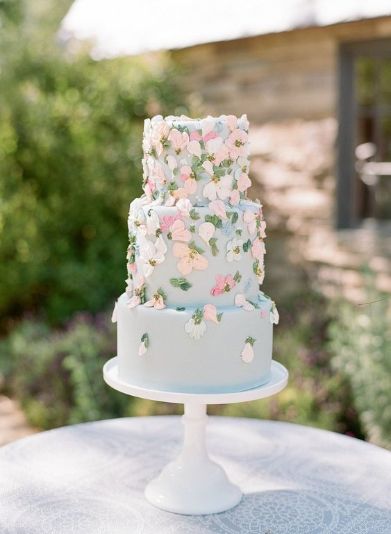 a pastel blue wedding cake with pastel sugar blooms and leaves is a lovely and delicate dessert for a secret garden wedding